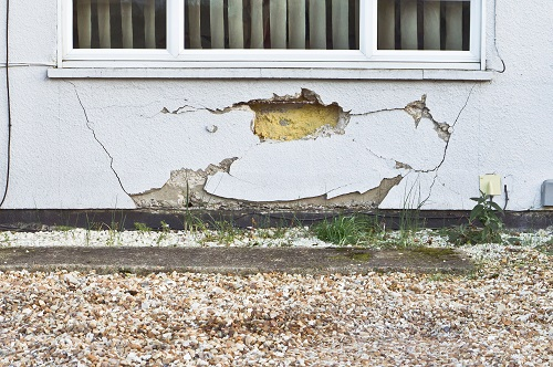 A wall with a window and large subsidence damage underneath on the wall