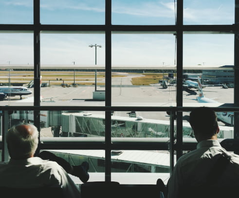 Two men waiting in airport terminal looking out to planes