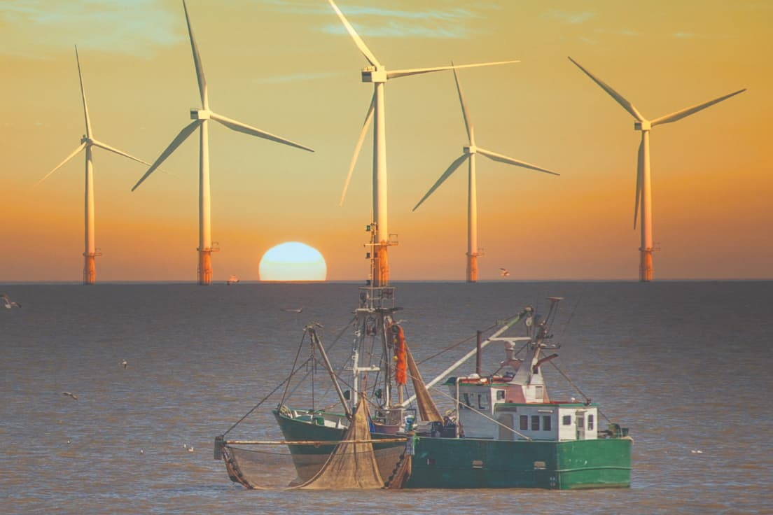 offshore windfarm at sunset with fishing trawler in foreground