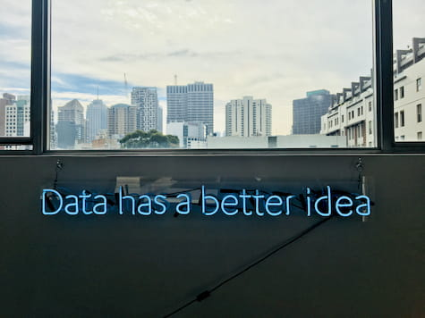 Text saying Data has a better idea as a neon light below window looking out at a city of high rise buldings