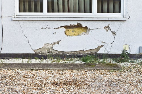 Hole in wall of house with additional cracks due to subsidence